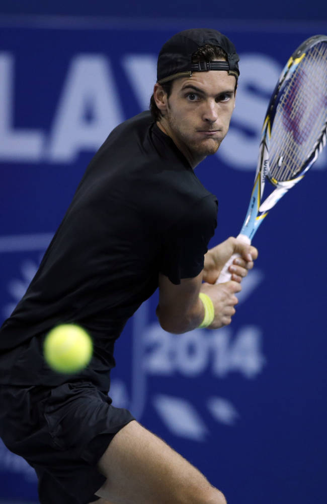Joao Sousa of Portugal returns a shot against Julien Benneteau of France during their final match at the Malaysian Open tennis tournament in Kuala Lumpur, Malaysia, Sunday, Sept. 29, 2013