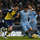 Manchester City's Sergio Aguero, right, takes the ball past Arsenal's Laurent Koscielny during the English Premier League soccer match between Manchester City and Arsenal at the Etihad Stadium, Manchester, England, Sunday, Jan. 18, 2015