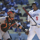 Los Angeles Dodgers' Juan Uribe, right, reacts while being tagged by San Francisco Giants catcher Buster Posey after he struck out during the eighth inning of a baseball game on Friday, April 4, 2014, in Los Angeles The Associated Press