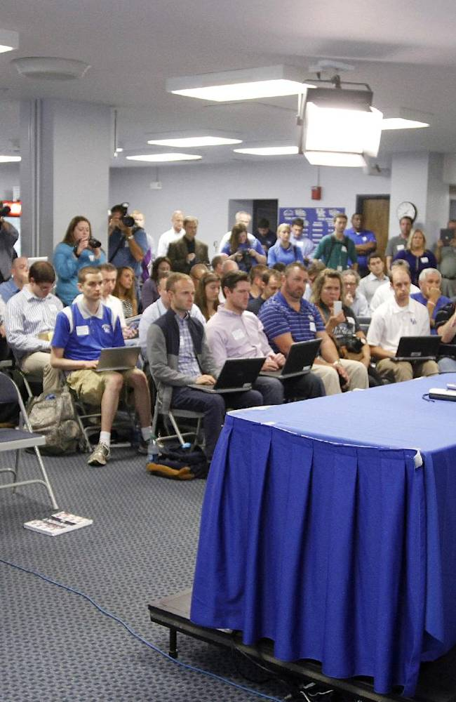 Kentucky coach John Calipari, right, addresses a reporter's question during the NCAA men's college basketball team's media day Tuesday, Oct. 15, 2013, in Lexington, Ky