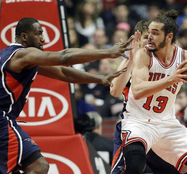 Chicago Bulls center Joakim Noah (13) drives against Atlanta Hawks forward Elton Brand, left, and Kyle Korver during the first half of an NBA basketball game in Chicago on Saturday, Jan. 4, 2014