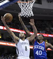 Brooklyn Nets' Deron Williams (8) drives to the basket and is fouled by Philadelphia 76ers' Jarvis Varnado during the first half of an NBA basketball game on Saturday, April 5, 2014, in Philadelphia. (AP Photo/Michael Perez)