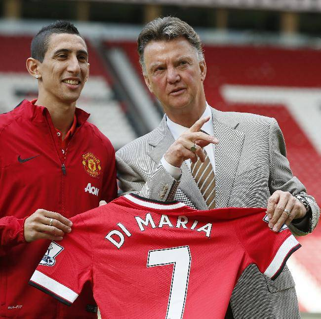 Manchester United's new player Angel Di Maria left, and manager Louis van Gaal, pose for photographers holding his new shirt, at Old Trafford Stadium in Manchester, England, Thursday, Aug. 28, 2014. Manchester United have signed winger Angel Di Maria from Real Madrid for a British record transfer fee of 59.7m. The Argentine winger had a medical in Manchester on Tuesday and has signed a five-year deal