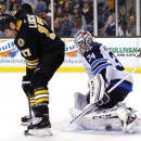 Winnipeg Jets goalie Michael Hutchinson, right, makes a save while being screened by Boston Bruins' Milan Lucic during overtime of the Boston Bruins 2-1 win over the Winnipeg Jets in an NHL hockey game in Boston, Friday, Nov. 28, 2014. (AP Photo/Winslow Townson)