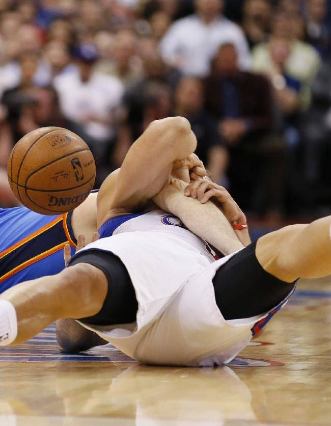Los Angeles Clippers forward Blake Griffin fights on the floor for a loose ball with Oklahoma City Thunder forward Nick Collison during the first half of an NBA basketball game in Los Angeles, Wednesday, April 9, 2014. The play resulted in a jump ball