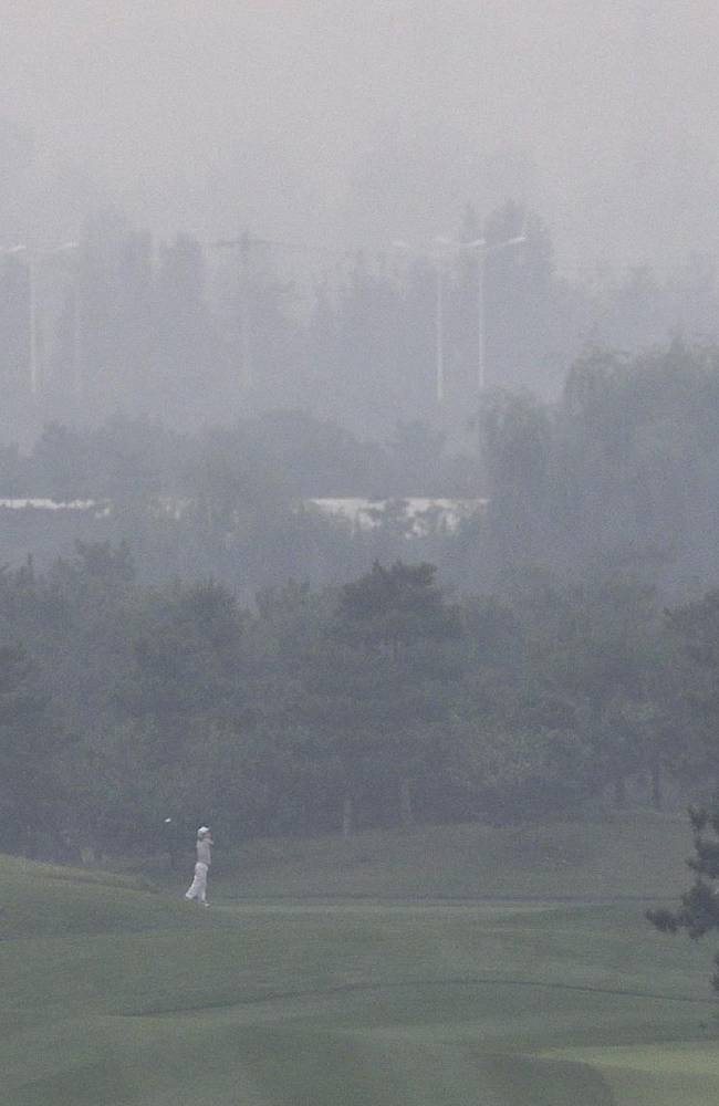 A golfer plays on the court on a hazy day at Pine Valley Golf Club on the outskirts of Beijing, China, Sunday, Oct. 6, 2013. Fog and pollution descended on northern China on Sunday, forcing international golf and tennis players to play in hazardous smog and leading to flight cancellations and road closures as millions of Chinese headed home from a national holiday
