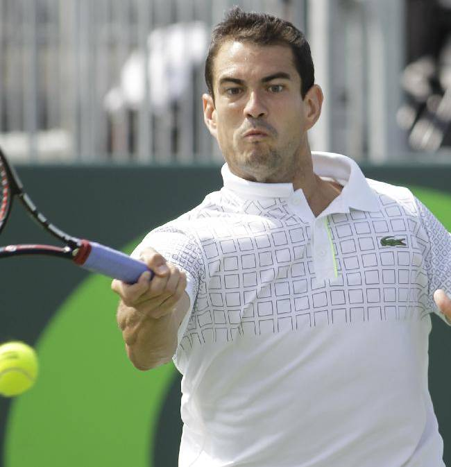 Guillermo Garcia-Lopez, of Spain, returns the ball to Milos Raonic, of Canada, during the Sony Open tennis tournament, Monday, March 24, 2014, in Key Biscayne, Fla