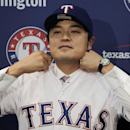 In this Dec. 27, 2013, file photo, Shin-Soo Choo, of South Korea, adjusts the collar of his Texas Rangers jersey during a news conference announcing his signing at the team's headquarters in Arlington, Texas. Spring training is starting, and it's time for