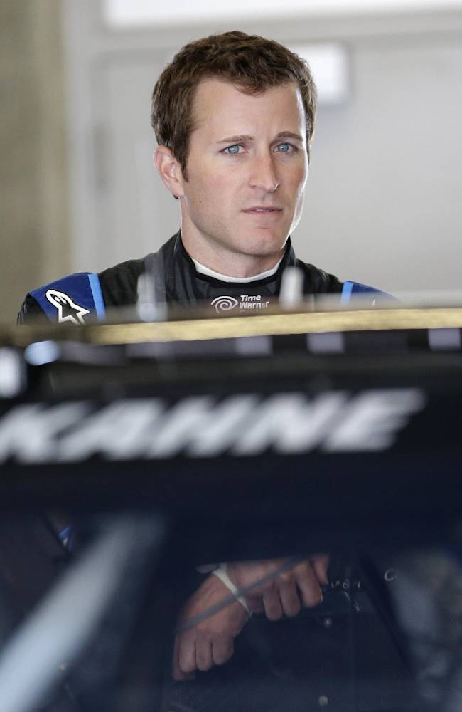 Driver Kasey Kahne waits by his car before practice for the Brickyard 400 Sprint Cup series auto race at the Indianapolis Motor Speedway in Indianapolis, Friday, July 25, 2014