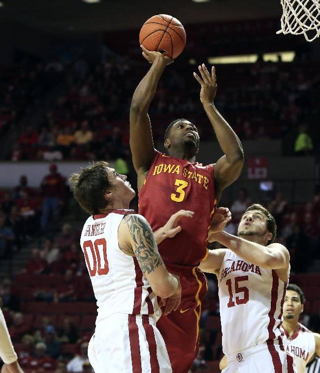 Iowa State forward Melvin Ejim (3) goes to the basket between Oklahoma's Ryan Spangler (00) and Tyler Neal (15) during the first half of an NCAA college basketball game in Norman, Okla. on Saturday, Jan. 11, 2014
