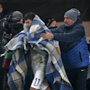 Aa assistant covers by a blanket Dinamo Moscow's Aleksei Ionov, center, as he leaves the field during the Europa League Group E soccer match between Dynamo Moscow and Panathinaikos at the Arena Khimki stadium in Moscow, Russia, Thursday, Nov. 27, 2014 The