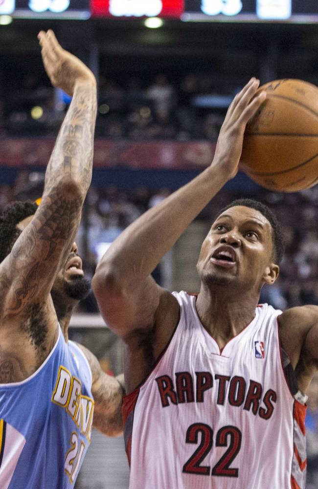 Toronto Raptors' Rudy Gay, right, shoots as Denver Nuggets' Wilson Chandler defends during the second half of an NBA basketball game on Sunday, Dec. 1, 2013, in Toronto