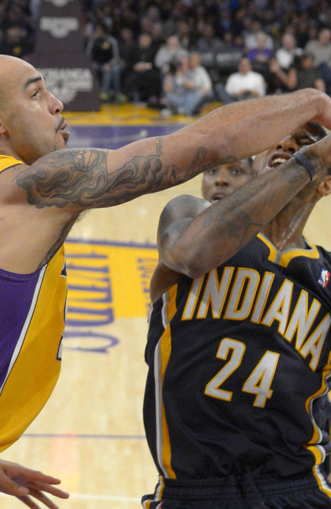 Indiana Pacers forward Paul George, right, puts up a shot as Los Angeles Lakers center Robert Sacre defends during the second half of an NBA basketball game, Tuesday, Jan. 28, 2014, in  Los Angeles
