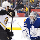 Toronto Maple Leafs goalie James Reimer (34) eyes the puck with Boston Bruins forward Reilly Smith, left, during third-period NHL hockey game action in Toronto, Saturday, Oct. 25, 2014 The Associated Press
