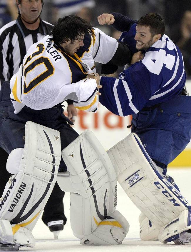 Buffalo Sabres goalie Ryan Miller fights with Toronto Maple Leafs goalie Jonathan Bernier during the third period of an NHL hockey preseason game in Toronto, Sunday Sept. 22, 2013