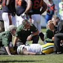 Trainers tend to Green Bay Packers defensive end Josh Boyd (93) after an injury in the first half of an NFL football game against the Chicago Bears Sunday, Sept. 28, 2014, in Chicago. The Associated Press