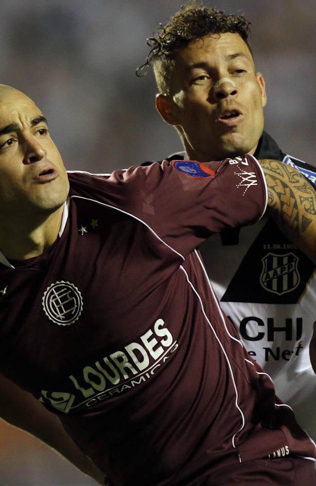 Baraka of Brazil's Ponte Preta, right, and Santiago Silva of Argentina's Lanus fight for the ball during the first leg match of Copa Sudamericana final in Sao Paulo, Brazil, Wednesday, Dec. 4, 2013. The game ended 1-1