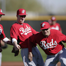 Cincinnati Reds first baseman Joey Votto, right, jokes with third baseman Todd Frazier, center, and shortstop Zack Cozart, left, during a spring training baseball workout Thursday, Feb. 20, 2014, in Goodyear, Ariz The Associated Press