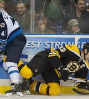 Boston Bruins defenseman Zdeno Chara goes down to the ice after colliding with Winnipeg Jets forward Devin Setoguchi during the first period of an NHL hockey preseason game Friday, Sept. 27, 2013, in Saskatoon, Saskatchewan. (AP Photo/The Canadian Press, Liam Richards)