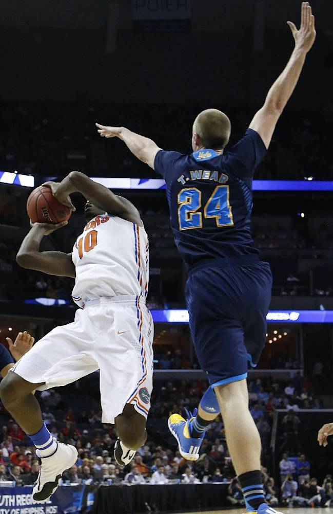 Florida forward Dorian Finney-Smith (10) shoots against UCLA forward Travis Wear (24) during the first half in a regional semifinal game at the NCAA college basketball tournament, Thursday, March 27, 2014, in Memphis, Tenn