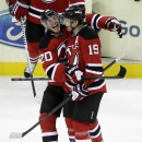 New Jersey Devils center Ryan Carter (20) and center Travis Zajac (19) celebrate Zajac's shootout goal that gave the Devils a 2-1 victory over the New York Islanders during a preseason NHL hockey game, Thursday, Oct. 2, 2014, in Newark, N.J The Associated