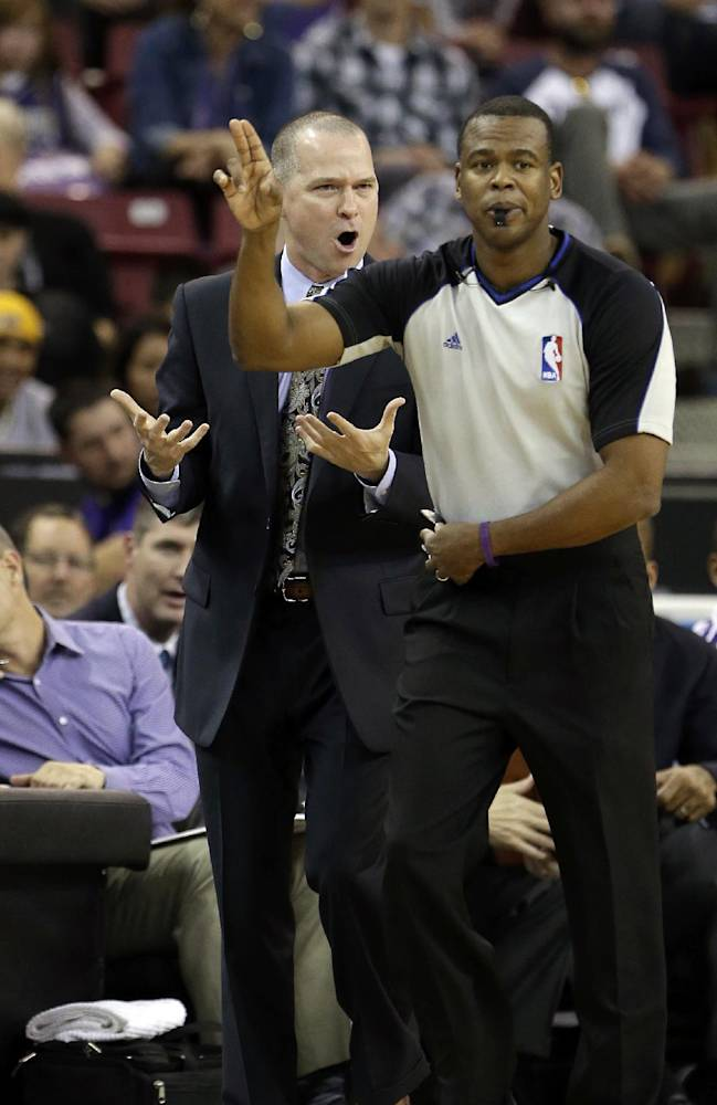 Sacramento Kings head coach Michael Malone, left, talks to Official Sean Wright about a foul called against his team during the first quarter of an NBA basketball game against the Golden State Warriors in Sacramento, Calif., Sunday, Dec. 1, 2013