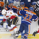 Calgary Flames' Dennis Wideman (6) is checked by Edmonton Oilers' Matt Hendricks (23) during the second period of an NHL hockey game Saturday, March 1, 2014, in Edmonton, Alberta The Associated Press