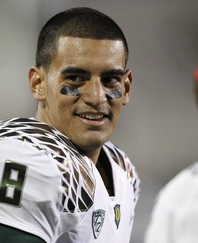 Oregon starting quarterback Marcus Mariota jokes with teammates as he watches from the sideline during the fourth quarter of Oregon's 57-16 victory over Colorado in an NCAA college football game in Boulder, Colo., on Saturday, Oct. 5, 2013