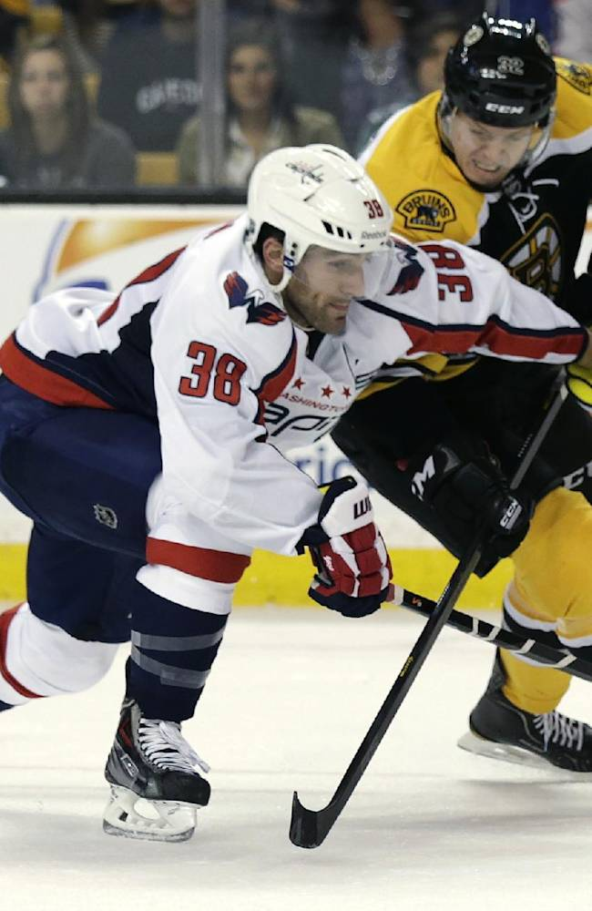 Washington Capitals defenseman Jack Hillen, left, tries to keep Boston Bruins right wing Nick Johnson, right, away from the puck during the second period of an NHL preseason hockey game, Monday, Sept. 23, 2013, in Boston