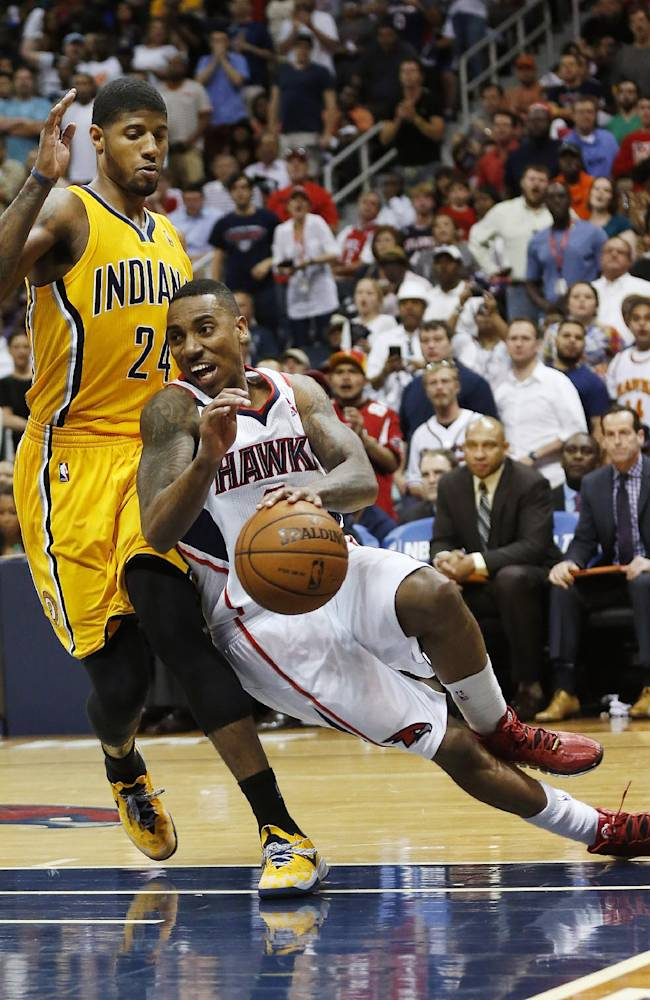 Atlanta Hawks guard Jeff Teague, right, slips as he drives past Indiana Pacers forward Paul George (24) in the second  half of Game 4 of an NBA basketball first-round playoff series, Saturday, April 26, 2014, in Atlanta. The Pacers won 91-88 to even the series at 2 games apiece