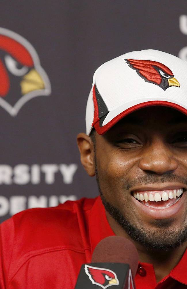 Antonio Cromartie smiles as he is introduced as an Arizona Cardinals football player during a news conference at the team's training facility, Thursday, March 20, 2014, in Tempe, Ariz