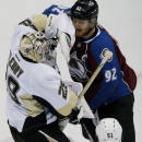 Pittsburgh Penguins goalie Marc-Andre Fleury, left, makes a glove-save of a redirected shot off the stick of Colorado Avalanche left wing Gabriel Landeskog, right, of Sweden, as Penguins defenseman Derrick Pouliot comes in to cover from the front in the first period of an NHL hockey game Wednesday, March 4, 2015, in Denver. (AP Photo/David Zalubowski)