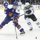 New York Islanders defenseman Lubomir Visnovsky (11) and Dallas Stars center Tyler Seguin (91) chase the puck during the first period of an NHL hockey game, Saturday, Oct. 25, 2014, in Uniondale, N.Y The Associated Press