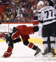 Phoenix Coyotes' Oliver Ekman-Larsson (23), of Sweden, gets upended by Los Angeles Kings' Jeff Carter (77) near the boards during the first period of an NHL hockey game, Tuesday, Jan. 28, 2014, in Glendale, Ariz. (AP Photo/Ross D. Franklin)