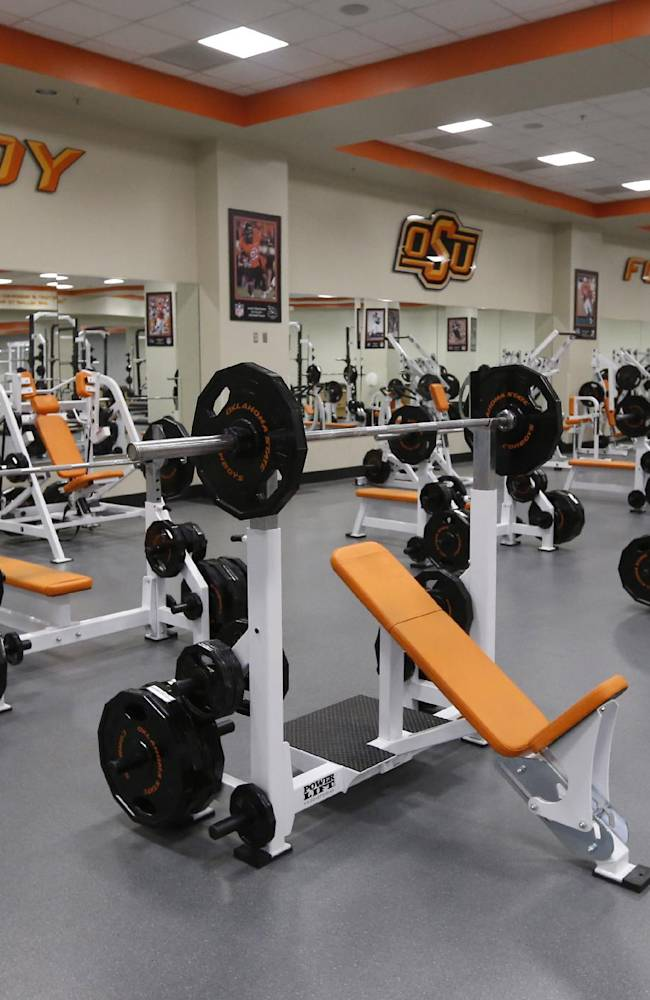 In this Sept. 5, 2013 photo, the football weight room is shown at Oklahoma State University in Stillwater, Okla. With weight rooms as big as football fields, more flat screen TVs than a Best Buy and enough leather furniture to fill Trump Plaza, players have no reason to go back to the dorms