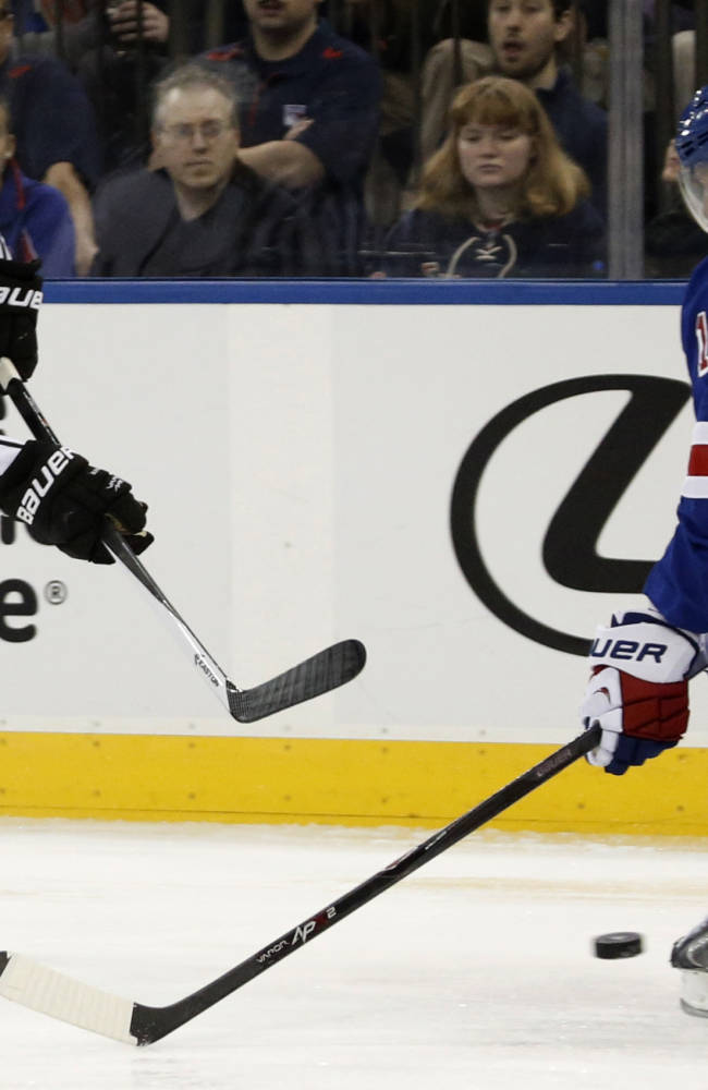 Los Angeles Kings right wing Matt Frattin (21) takes a shot from mid ice as New York Rangers defenseman Marc Staal (18) defends in the first period of their NHL hockey game at Madison Square Garden in New York, Sunday, Nov. 17, 2013