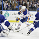 Edmonton Oilers center Ryan Nugent-Hopkins (93) moves the puck between Tampa Bay Lightning goalie Ben Bishop (30) and defenseman Matt Carle (25) during the first period of an NHL hockey game Thursday, Jan. 15, 2015, in Tampa, Fla The Associated Press