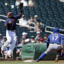 Texas Rangers' Shin-Soo Choo stops at third as Cleveland Indians' Carlos Santana leaps to make a catch during the first inning of a spring exhibition baseball game Tuesday, March 25, 2014, in Goodyear, Ariz The Associated Press
