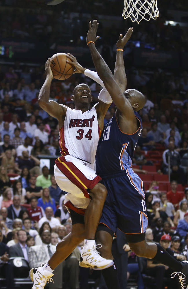 Charlotte Bobcats' Anthony Tolliver (43) blocks Miami Heat's Ray Allen (34) during the second half of an NBA basketball game in Miami, Monday, March 3, 2014. LeBron James scored a team record of 61 points. The Heat won 124-107