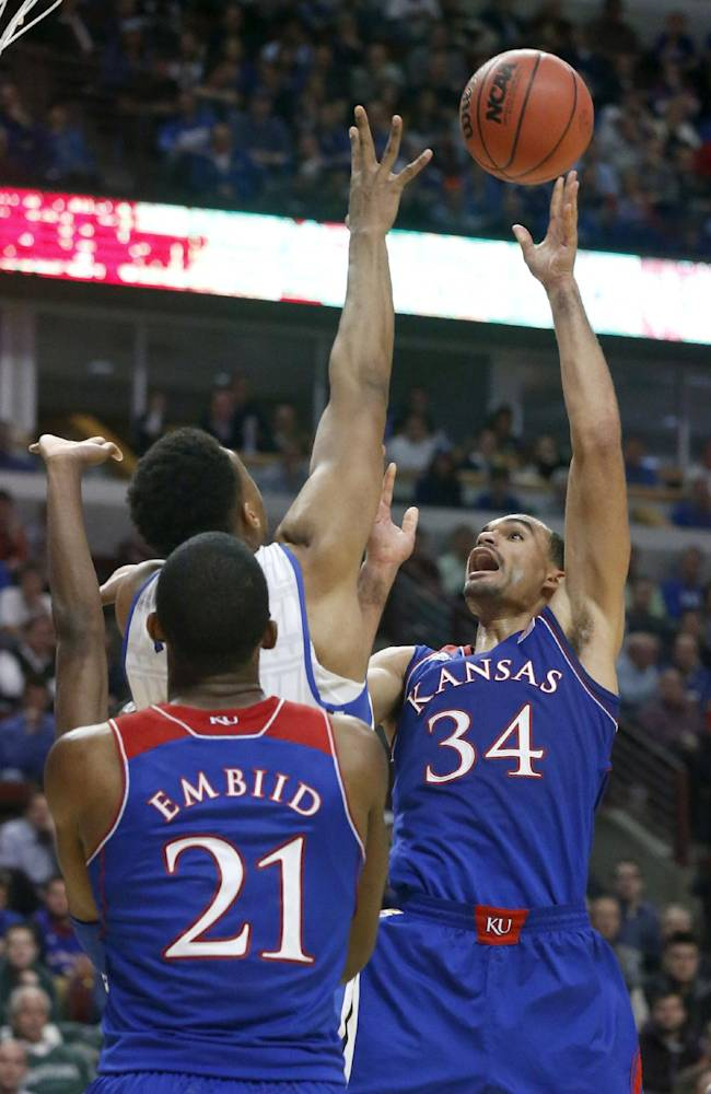 Kansas forward Perry Ellis (34) scores over Duke forward Jabari Parker as Joel Embiid watches during the second half of an NCAA college basketball game Tuesday, Nov. 12, 2013, in Chicago. Kansas won 94-83