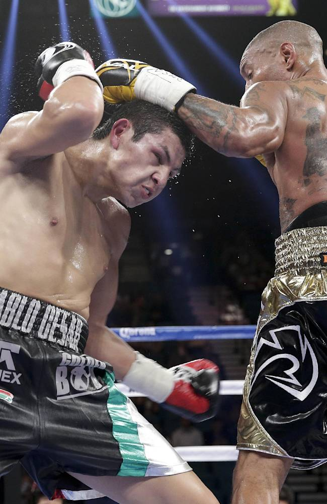 Pablo Cesar Cano, left, throws body punches against Ashley Theophane in the third round during a welterweight fight, Saturday, Sept. 14, 2013, in Las Vegas