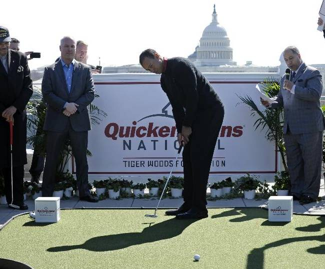 Tiger Woods, center, putts during a putting challenge at the Newseum in Washington, Monday, March 24, 2014. Woods and Quicken Loans Chief Executive Officer Bill Emerson, second from left, participated in the putting challenge to have the mortgage payments paid for three military families for one month. Earlier, Woods and Emerson announced that Quicken Loans had signed a multi-year agreement to become the title sponsor of the Quicken Loans National to be played at Congressional Country Club in Bethesda, Md., in June