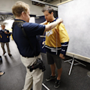 Nashville Predators defenseman and team captain Shea Weber has his jersey adjusted by team photographer John Russell on the first day of NHL hockey training camp on Thursday, Sept. 18, 2014, in Nashville, Tenn. The Predators officially kick off a new era