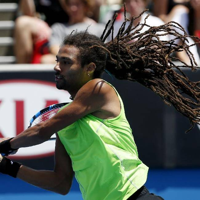 Dustin Brown of Germany's hair flies up as he plays Grigor Dimitrov of Bulgaria during their first round match at the Australian Open tennis championship in Melbourne, Australia, Monday, Jan. 19, 2015