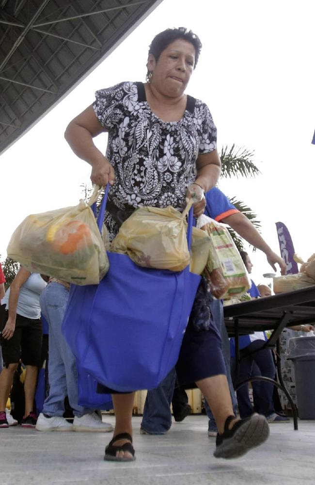 Betty Trujillo carries bags of goods during the annual Miami Marlins Ayudan Turkey Distribution at Marlins Park, Friday, Nov. 22, 2013, in Miami. The Marlins and sponsors distributed 1,000 turkeys and Thanksgiving Day fixings to ballpark neighbors