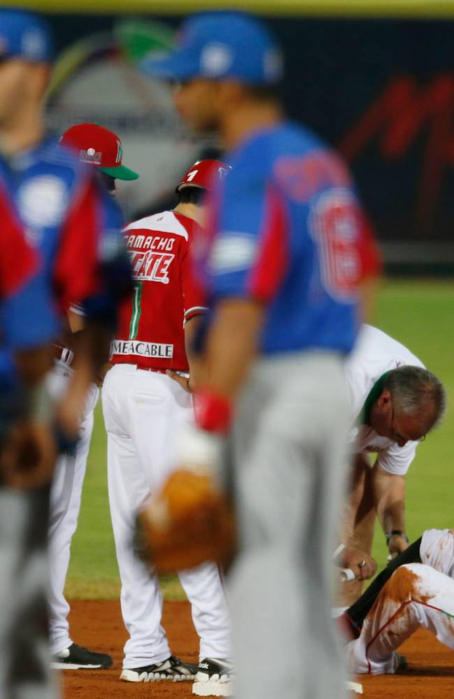 Mexico outfielder Chris Roberson, right, is tended to by the team's doctor during a Caribbean Series baseball semifinal game against the Dominican Republic in Porlamar, Venezuela, Thursday, Feb. 6, 2014