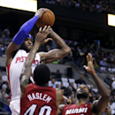 Detroit Pistons forward Josh Smith, top left, is forced to pass the ball against Miami Heat defenders Udonis Haslem (40) and LeBron James (6) during the first half of an NBA basketball game Friday, March 28, 2014, in Auburn Hills, Mich. The Heat defeated