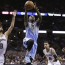 Denver Nuggets' Ty Lawson (3) drives past San Antonio Spurs' Tony Parker (9), of France, and Danny Green (4) to score during the second half of an NBA basketball game, Wednesday, March 27, 2013, in San Antonio. San Antonio won 100-99. (AP Photo/Eric Gay)
