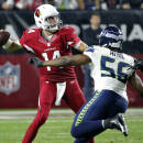 Arizona Cardinals quarterback Ryan Lindley (14) throws under pressure from Seattle Seahawks defensive end Cliff Avril (56) during the second half of an NFL football game, Sunday, Dec. 21, 2014, in Glendale, Ariz. (AP Photo/Ross D. Franklin)