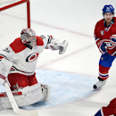 Montreal Canadiens center David Desharnais (51) goes after a loose puck as Carolina Hurricanes goalie Cam Ward (30) looks on during the first period of an NHL hockey game Tuesday, Dec. 16, 2014, in Montreal The Associated Press